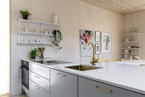 Harmaa keittiö modernissa puutalossa.